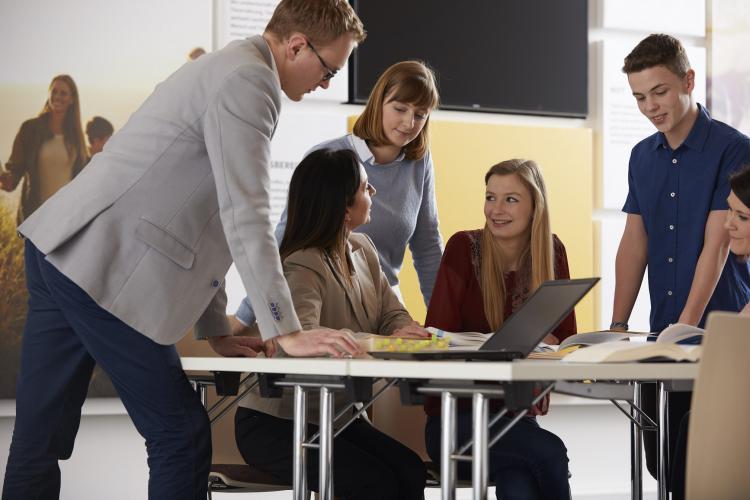 Ein Team arbeitet zusammen an einem Schreibtisch.