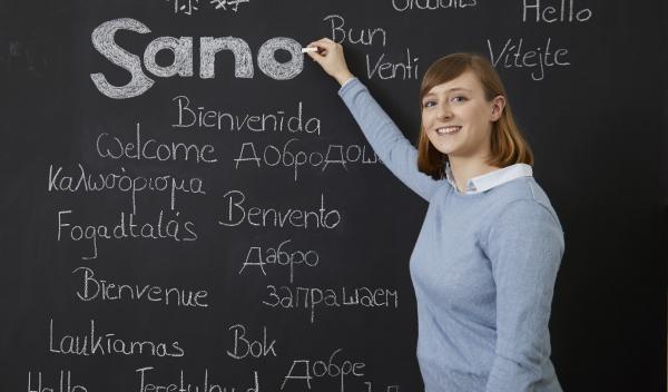 """Das Foto zeigt ein Mädchen, das Sano mit einer Kreide auf die Tafel schreibt. Auf der Tafel steht auch noch ,,Herzlich Willkommen"""" in verschiedenen Sprachen."""