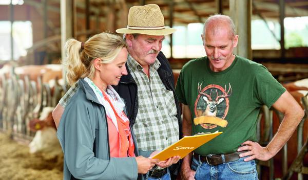Landwirte und Sano Fachberaterin beim Gespräch im Kuhstall.
