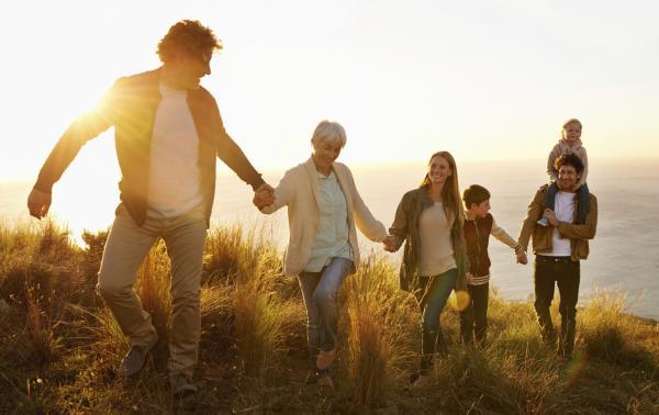 Famile und Freunde, die sich an der Hand nehmen und gemeinsam bei Sonnenuntergang die Dünen am Meer entlang gehen.